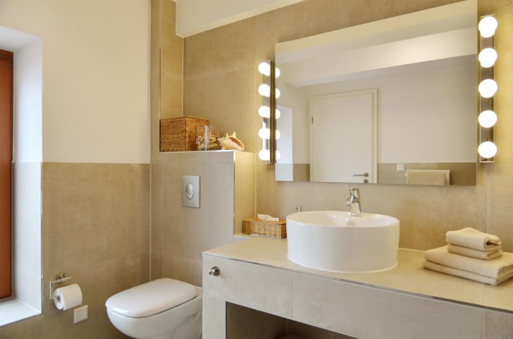Modernes Badezimmer mit rundem Aufsatzwaschbecken und Theaterspiegel