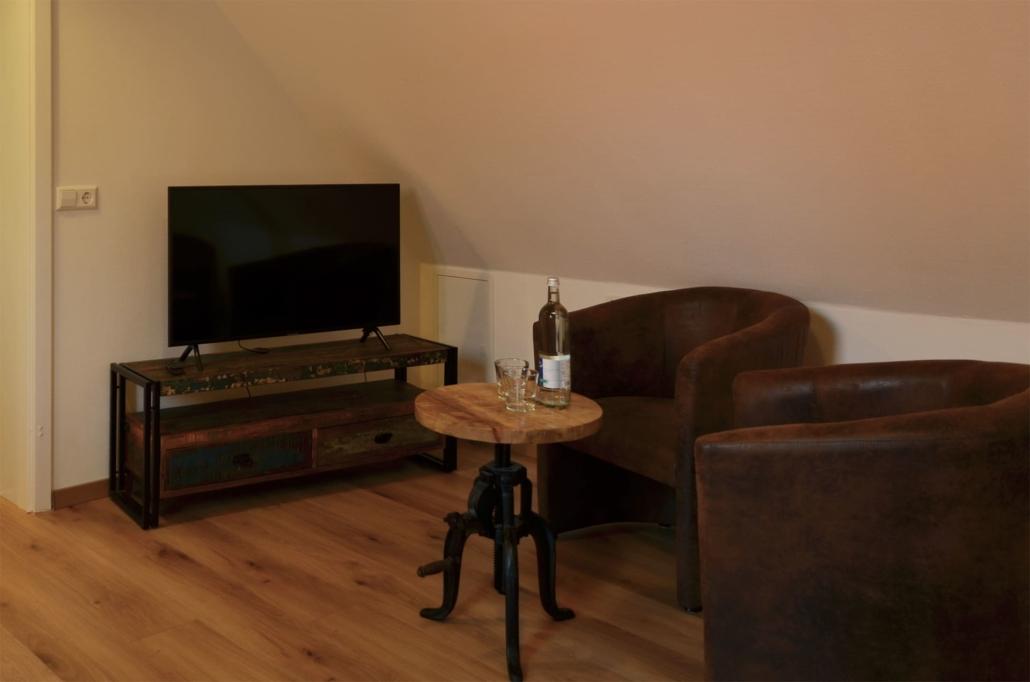 Kleiner Sitzbereich mit zwei Ledersesseln und Beistelltisch zum ausruhen. Ein moderner Smart-TV sorgt auf Wunsch für Unterhaltung
